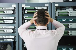 A man stressing in a server room