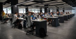 A picture of an office full of people working on laptops