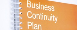 A note pad which has the words 'Business Continuity Plan' on the front of it