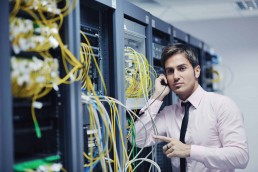 A man sorting out cables in a server room